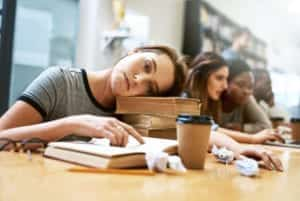 Portrait of a young woman looking tired while studying in a college library - www.canineassistedlearning.com